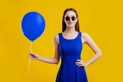 Młoda kobieta z lotniczym balonem nad żółtym tłem obrazy royalty free