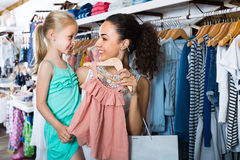 Młoda kobieta z małą dziewczyną wybiera menchie ubiera w dzieciak odzieży zdjęcia stock