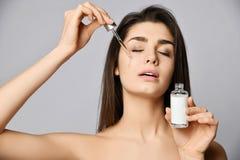 Młoda kobieta z oczami zamykającymi z przyjemnością odnowienie krople kryształ - jasny kosmetyk dla skóry od pipety na jej twarzy obraz royalty free