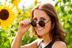 Młoda kobieta z okularami przeciwsłonecznymi śmia się w słonecznika polu fotografia stock