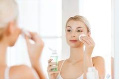 Młoda kobieta z płukanki domycia twarzą przy łazienką Obrazy Royalty Free