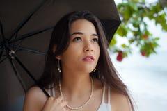 Młoda kobieta z parasolem na deszczowym dniu plażą obraz stock