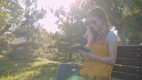 Młoda kobieta z pastylką na ławce zdjęcie wideo