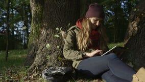 Młoda kobieta z pastylka komputerem w pięknym jesień parku