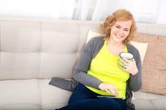 Młoda kobieta z pastylka pecetem na kanapie fotografia royalty free