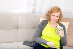 Młoda kobieta z pastylka pecetem na kanapie obraz royalty free