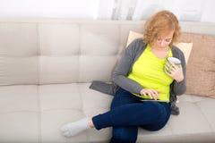 Młoda kobieta z pastylka pecetem na kanapie zdjęcia stock