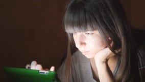 Młoda kobieta z pastylki komputerowym lying on the beach na kanapie Dziewczyna używa pastylka komputer nocnego w domu Rozjarzony  zdjęcie wideo