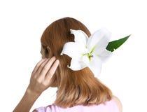 Młoda kobieta z pięknym leluja kwiatem w jej włosy, odizolowywającym Fotografia Stock