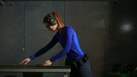 Młoda kobieta z pistoletem na salowym mknącym pasmie przygotowanie dla strzelać zbiory wideo