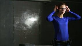 Młoda kobieta z pistoletem na salowym mknącym pasmie przygotowanie dla strzelać zbiory