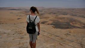Młoda kobieta z plecak pozycją na falezy ` s krawędzi i cieszyć się pustynnego widok zbiory wideo