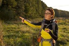 Młoda kobieta z plecakiem w łąkowym pokazuje sposobie Wycieczkować przy su fotografia stock