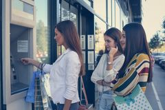 Młoda kobieta z przyjaciółmi bierze pieniądze od gotówkowej maszyny obraz stock