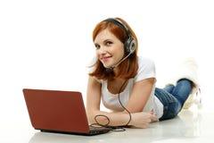 Młoda kobieta z słuchawki i laptopem. zdjęcia royalty free