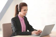 Młoda kobieta z słuchawki i laptopu działaniem obrazy stock