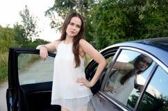 Młoda kobieta z samochodem parkującym na drodze gruntowej Fotografia Royalty Free