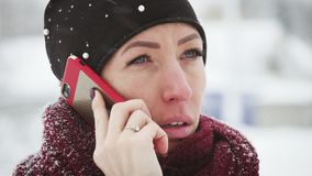 Młoda kobieta z smartphone i zima krajobrazem plenerowymi, Dziewczyna używa mobilnego smartphone plenerowego, śnieg spada zbiory wideo
