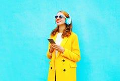 Młoda kobieta z smartphone słucha muzyka w hełmofonach zdjęcie royalty free