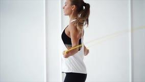 Młoda kobieta z sprawność fizyczna tropicielem na ręce jest skokowym arkaną w klubie sportowym zdjęcie wideo
