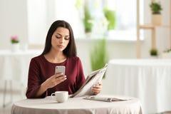 Młoda kobieta z telefon komórkowy czytelniczą wiadomością w kawiarni zdjęcia royalty free