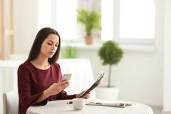 Młoda kobieta z telefon komórkowy czytelniczą wiadomością w kawiarni obraz stock