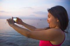 Młoda kobieta z telefon komórkowy kamerą bierze obrazek piękny plażowy zmierzch góry i krajobrazu Agung wulkan Bali w Azja ho Zdjęcia Royalty Free