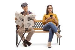 Młoda kobieta z telefonem komórkowym i starszym mężczyzną czyta gazetę na ławce obrazy royalty free