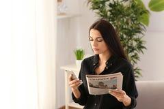 Młoda kobieta z telefonem komórkowym indoors i gazetą zdjęcie royalty free