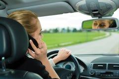 Młoda kobieta z telefonem w samochodzie Fotografia Royalty Free