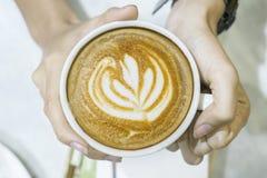 Młoda kobieta z tulipanowym rysunkiem na cappuccino obraz stock