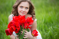 Młoda kobieta z tulipanowymi kwiatami fotografia stock