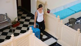 Młoda kobieta z walizką i plecakiem opuszcza hotel Końcówka wakacje zbiory wideo