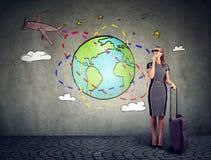 Młoda kobieta z walizką przygotowywającą podróżować dookoła świata samolotem Zdjęcia Royalty Free