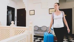 Młoda kobieta z walizki odprawą hotel obraz stock