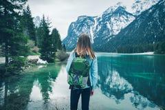 Młoda kobieta z zielonym plecakiem stoi na jeziorze obraz royalty free