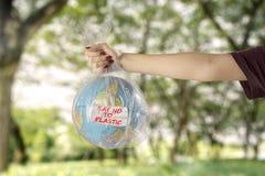 Młoda kobieta z ziemską kulą ziemską i plastikowym workiem zdjęcie royalty free
