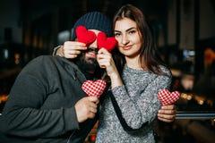 Młoda kobieta zakrywa jej chłopaka ` s ono przygląda się z czerwonymi poduszek sercami obrazy stock