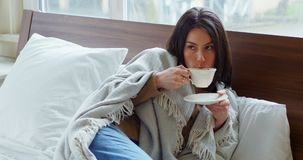 Młoda kobieta zawijająca w koc ma herbaty 4k zbiory wideo