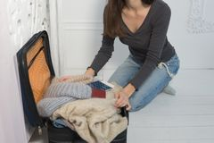Młoda kobieta zbiera walizkę Podróżnika narządzanie dla podróży, osobisty perspektywiczny widok ten wp8lywy od obrazy royalty free