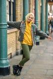 Młoda kobieta zbroi nastroszony cieszyć się w miastowym tle fotografia stock