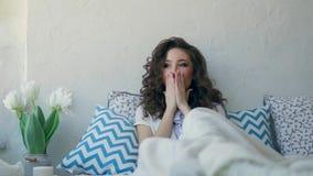Młoda kobieta ziewa, skupia się na poduszce i ono zakrywa z koc zbiory wideo