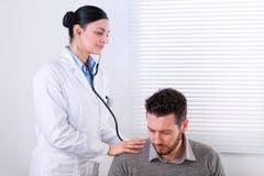 Młoda kobiety lekarka słucha bicie serca obrazy stock