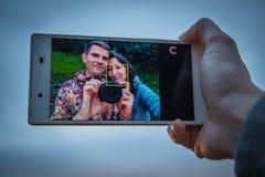 Młoda kochająca para robi selfie na telefon kamerze podczas gdy stojący Zdjęcia Royalty Free