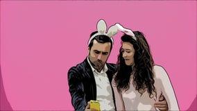 Młoda kochanek para na różowym tle Z osłuchanymi ucho na głowie Podczas to dziewczyna jest ubranym królików ucho zdjęcie wideo