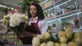 Młoda kwiaciarnia robi pięknemu kwiatu przygotowania zbiory