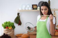 Młoda Latynoska kobieta w zielonym fartucha kucharstwie w kuchni podczas gdy dmuchający przy drewnianą łyżką Gospodyni domowa zak Zdjęcia Royalty Free