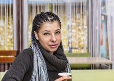 Młoda Latynoska szczęśliwa dziewczyna siedzi przy stołem w kawiarni obraz royalty free