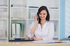 Młoda lekarz praktykujący lekarka pracuje przy kliniki recepcyjnym biurkiem, odpowiada rozmowy telefonicza i planuje spotkania Zdjęcie Stock