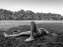 Młoda męska łyżwiarka odpoczywa na trawie z jego przygląda się zamkniętego zdjęcie stock